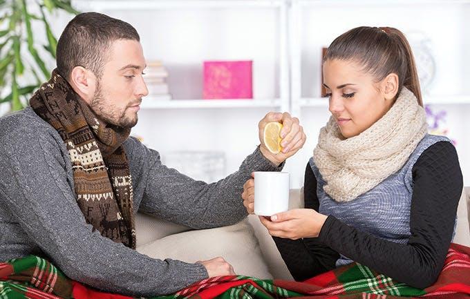 Phụ nữ bị cảm và chàng trai đem tách trà chanh