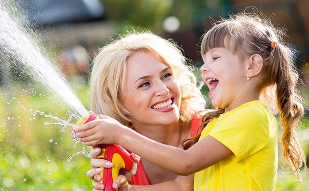 Người mẹ vui vẻ chơi nước cùng con gái trong vườn