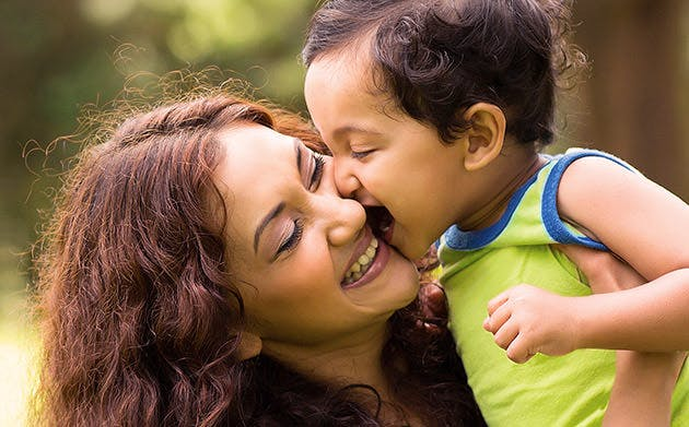 Cậu bé người Ấn Độ hôn người mẹ ở ngoài trời