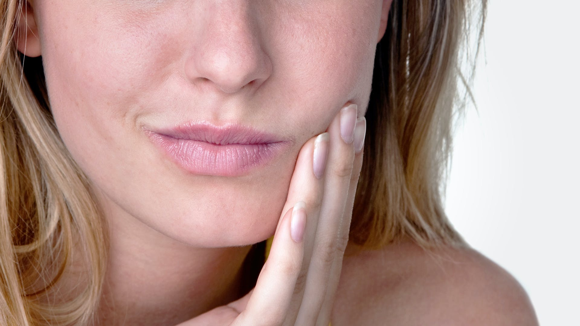 Frau mit Mundgeschwür, die linke Backe mit leidendem Ausdruck berührend.