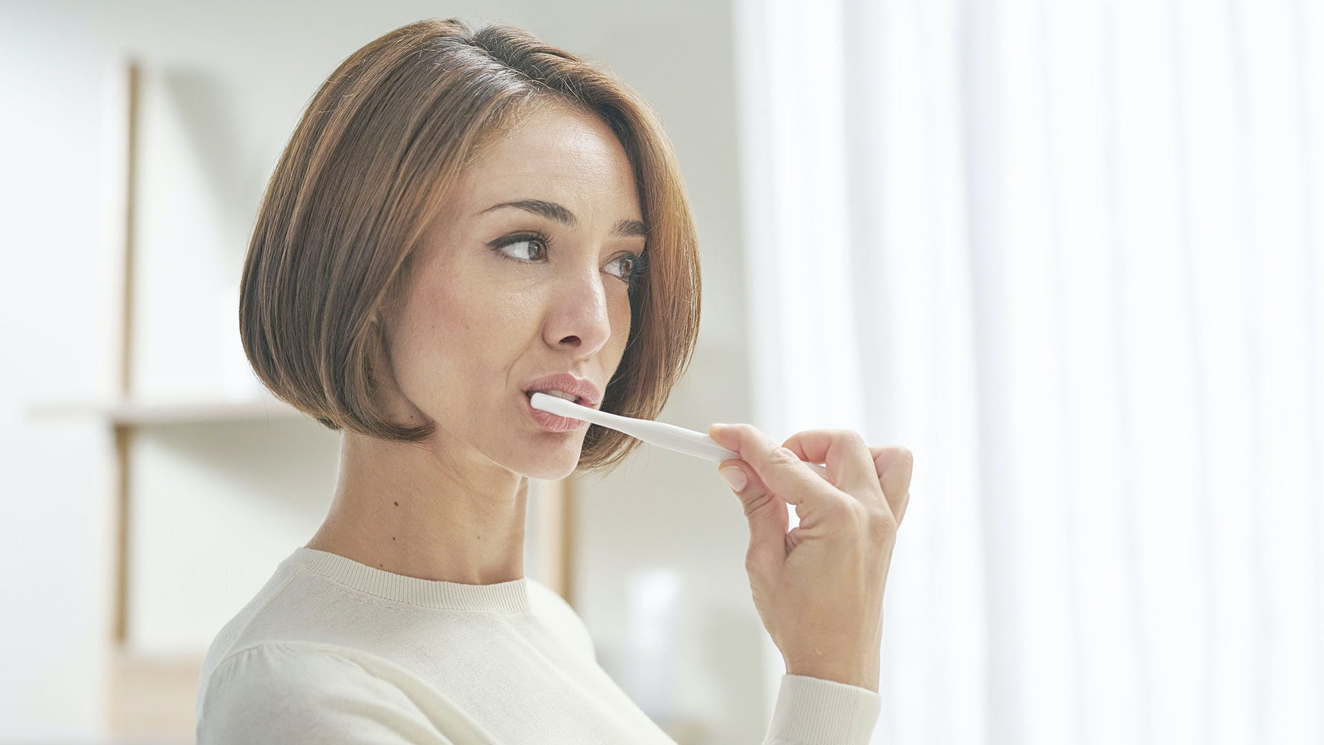 Frau beim Zähneputzen mit der Zahnpasta parodontax Complete Protection