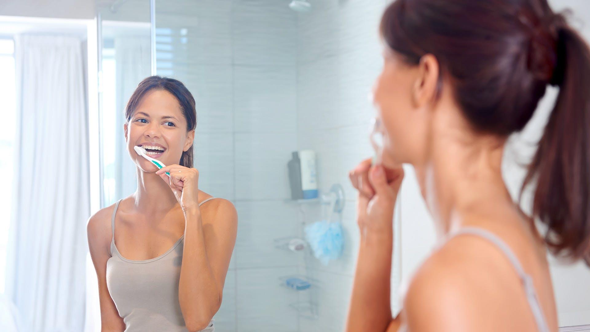 Lächelnde Frau beim Zähneputzen. Hier lesen: Zahnfleisch gesund halten.