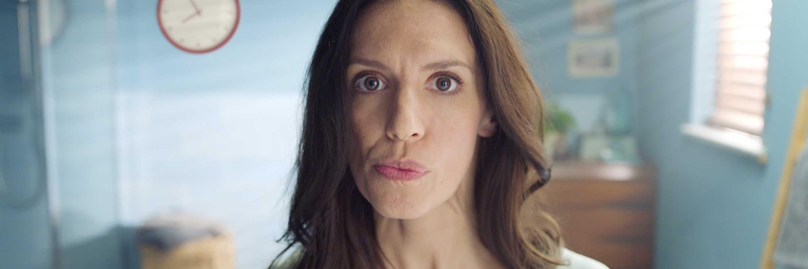 Frau mit Zahnfleischproblemen schaut in Spiegel