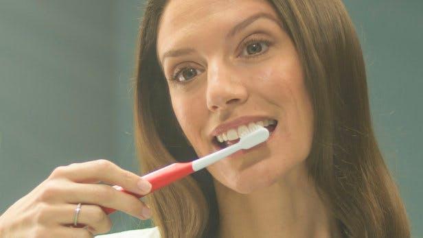 Mujer mirando al lavabo agarrando un cepillo de dientes