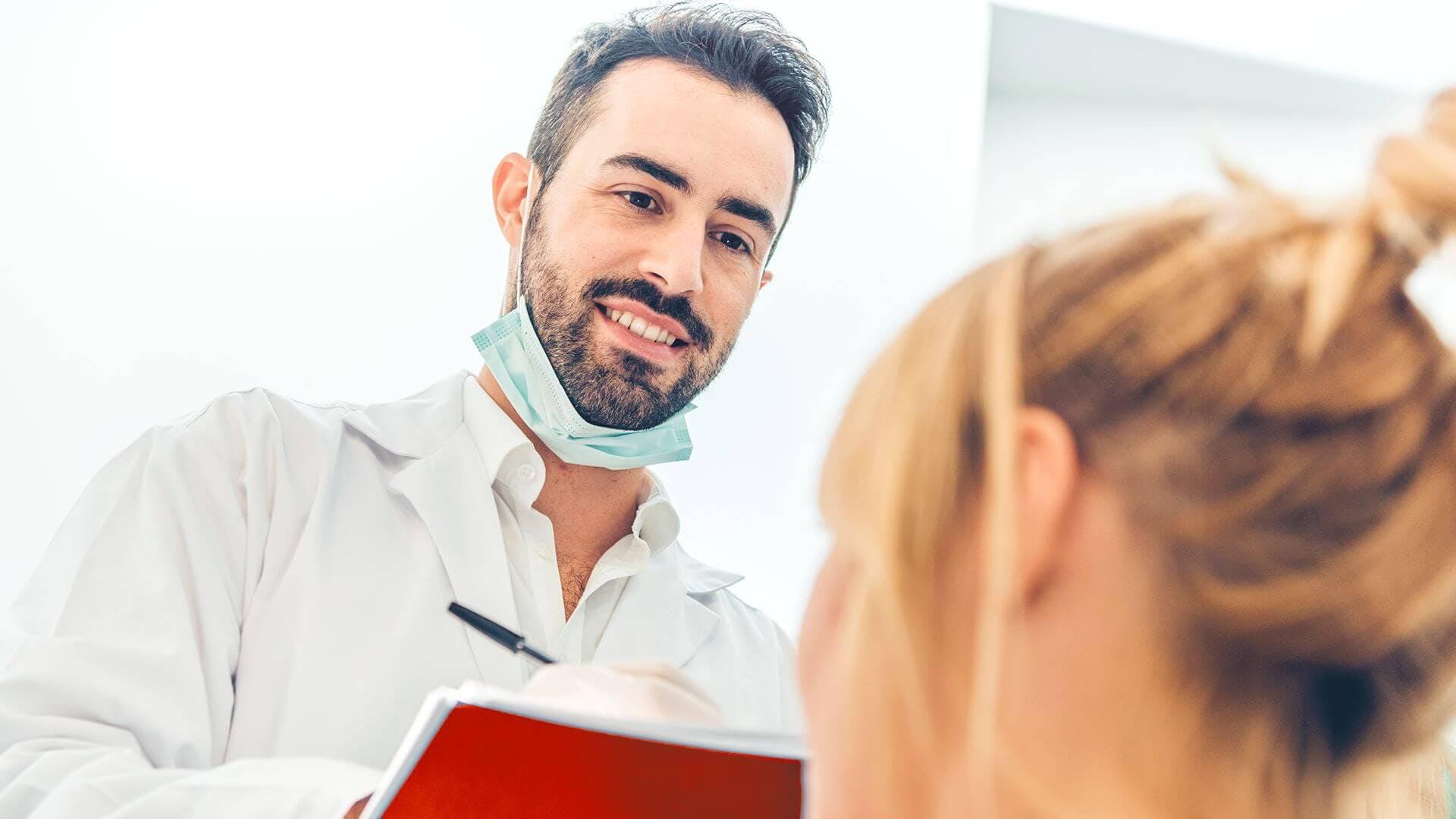 Pacientą dėl kraujuojančių dantenų konsultuojantis odontologas