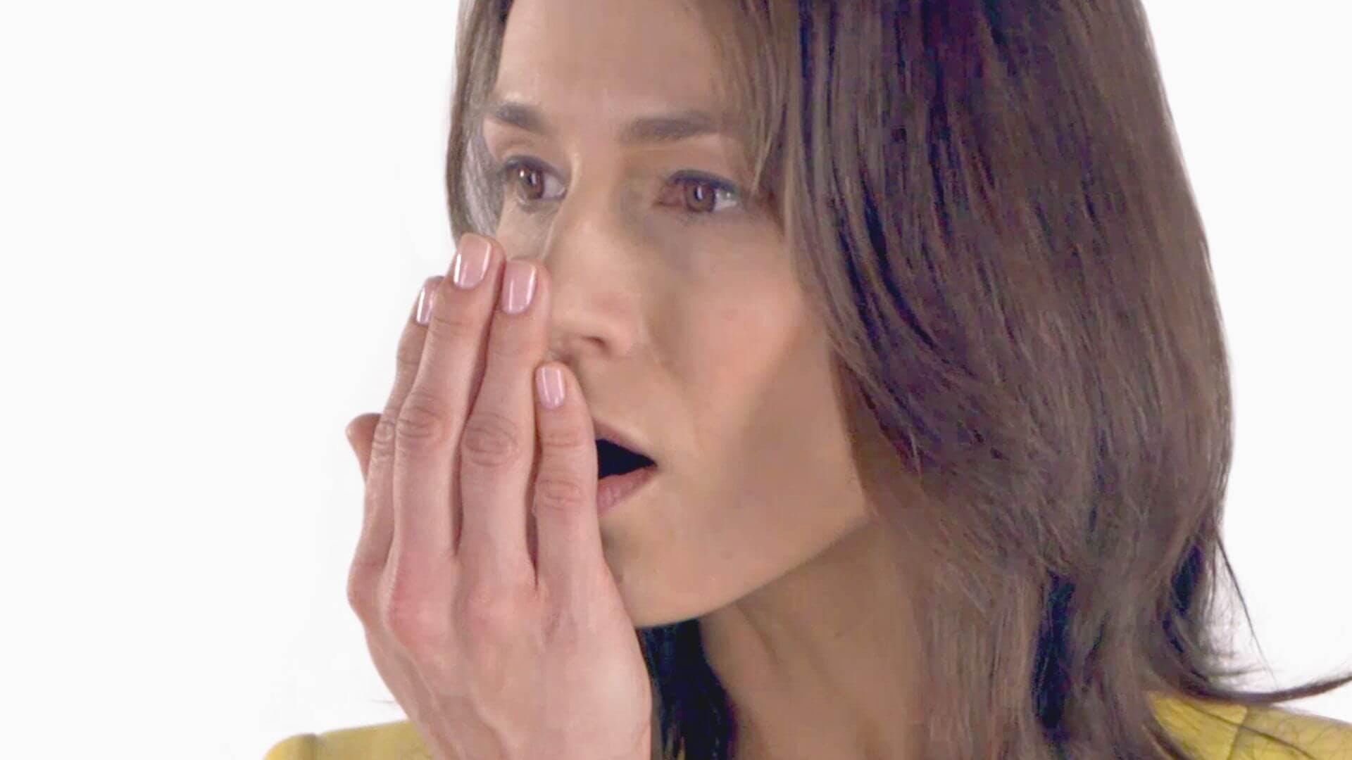 Kvinna som luktar på sin egen andedräkt