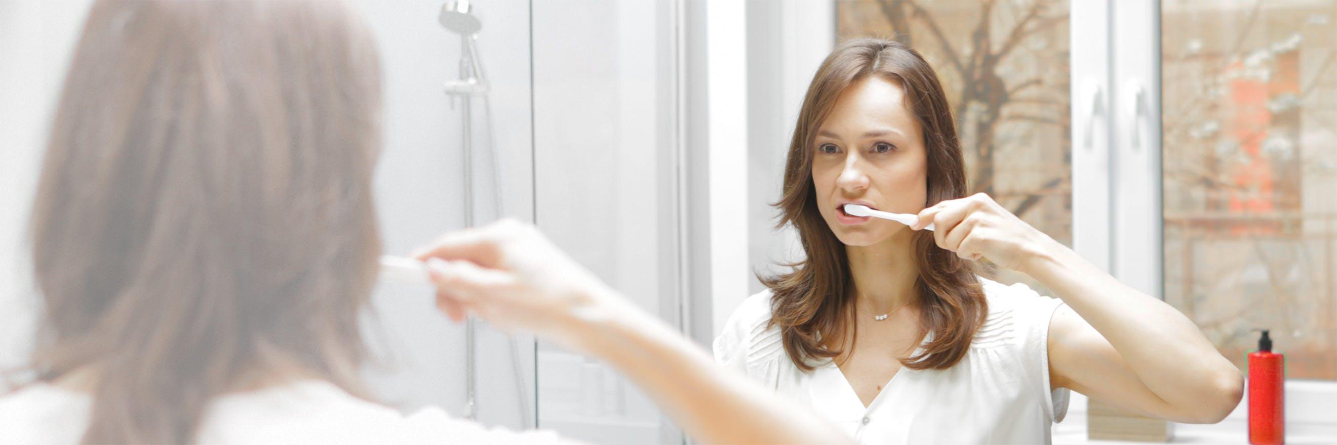 ผู้หญิงถือแปรงสีฟัน