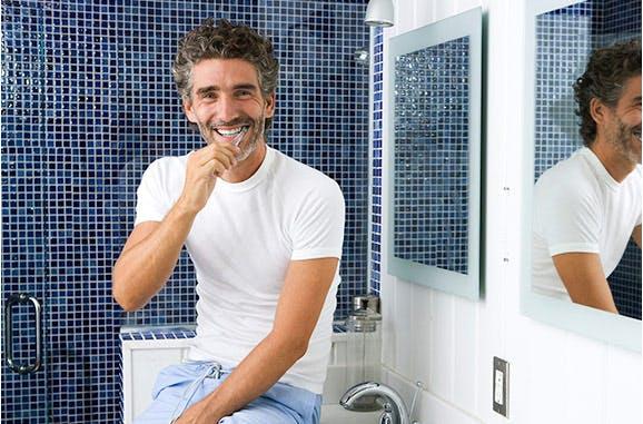 Hombre sonriendo cepillándose los dientes