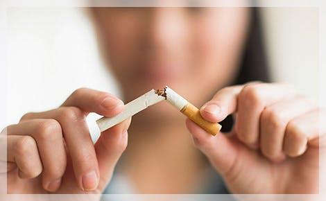 Mujer rompiendo un cigarrillo