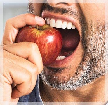 Hombre mordiendo una manzana