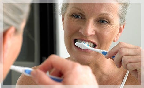 Elderly Woman Brushing Teeth Plaque Build Up parodontax