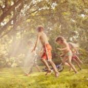 Children playing in water sprinkler