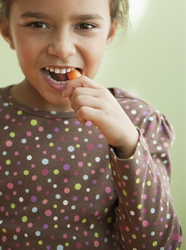 Petite fille croquant une mini-carotte