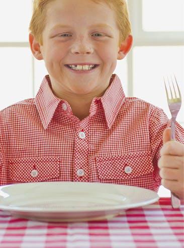 Jeune garçon tenant une fourchette et un couteau avant le repas