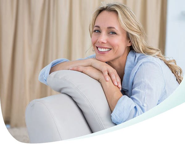 Blonde woman smiling on a grey coach and leaning her chin on hands