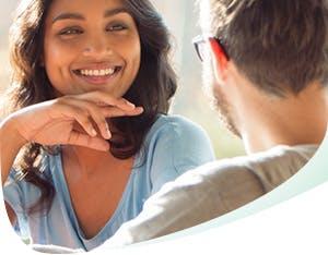 Une femme sourit à un homme en lui montrant des dents solides et blanches