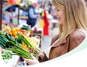 Femme au sourire éclatant qui choisit des légumes