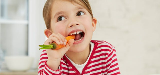 Petite fille croquant une carotte