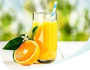 Du jus d'orange dans un verre et une moitié d'orange à côté