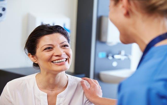 Femme souriante parlant à une professionnelle des soins dentaires