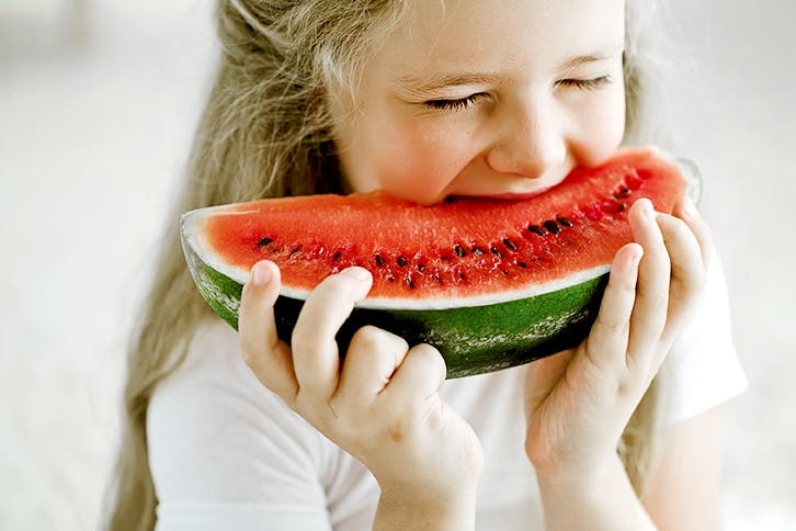 Small girl biting into a piece of watermelon