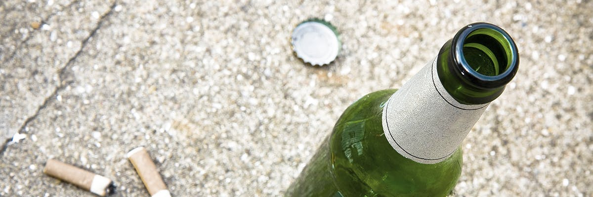 Empty beer bottle next to 2 cigarette butts on the cement.