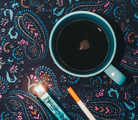 Cup of coffee on a table covered in a paisley tablecloth, sitting beside a cigarette and e-cigarette