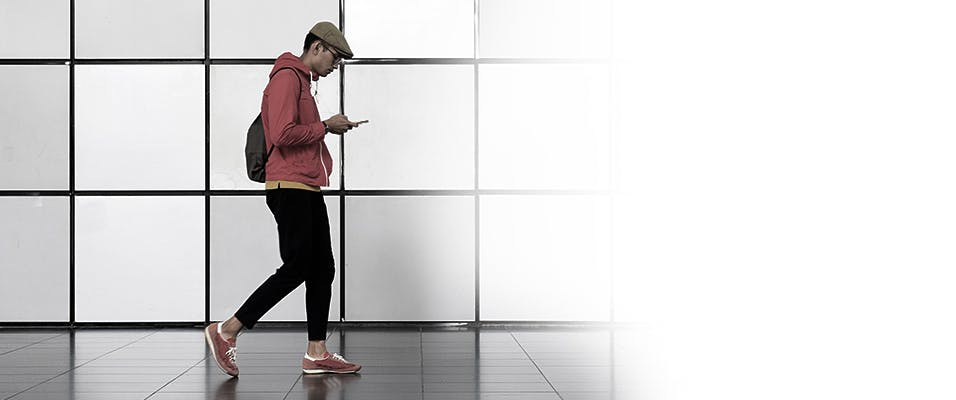 Man in red hoodie out walking with a cell phone