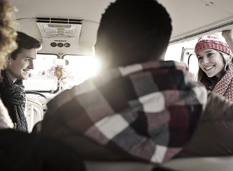 4 smiling people in a large van
