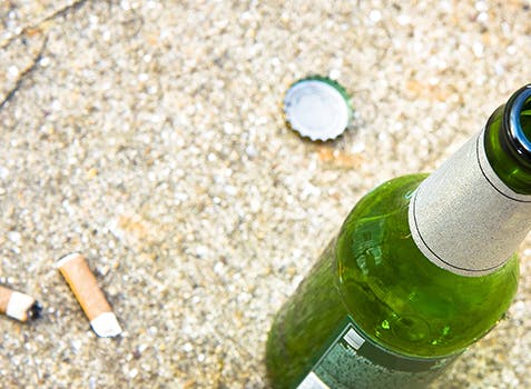 Beer bottle sitting on the ground beside 2 cigarette butts