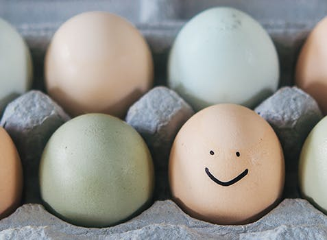 Carton of eggs with one that has a smiley face drawn on.