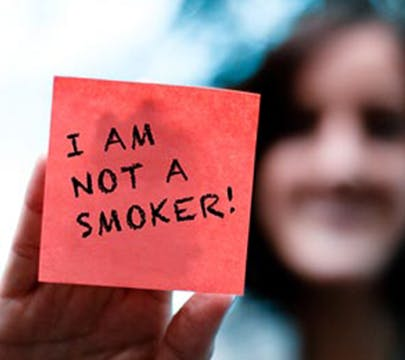 """Woman holding a post-it note up to some glass that says """"I AM NOT A SMOKER"""""""