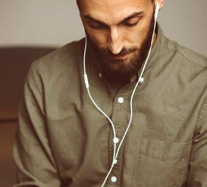 Man in a green shirt listening to headphones