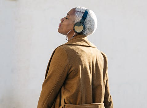 Woman standing with her head facing up toward the sky and her eyes closed, wearing headphones.