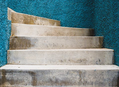 Stairs up between turquoise stucco walls