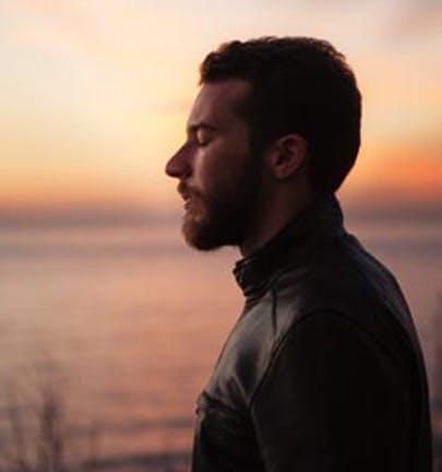 Man meditating outside by a lake during a beautiful sunrise