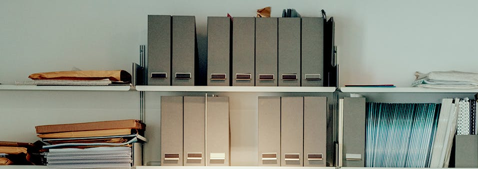 Two wall shelves full of work-related binders and paperwork