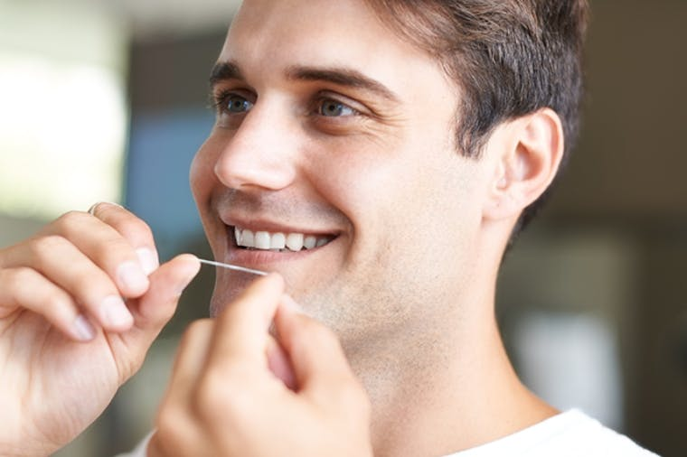 Man with tooth sensitivity to cold flossing