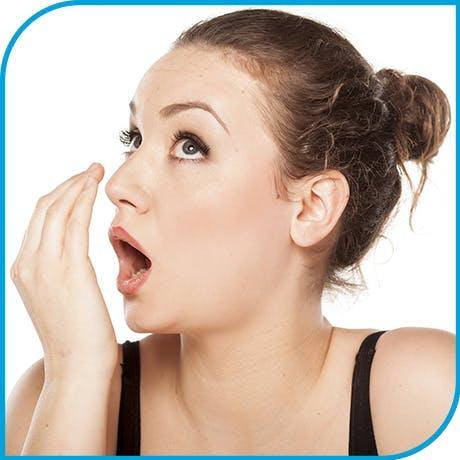 Woman checking for halitosis
