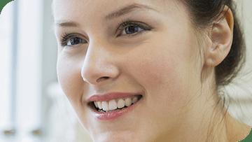Jeune fille souriante. On peut avoir des dents saines sans caries mais avec un émail abîmé.