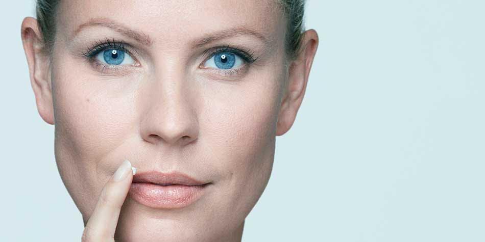 Woman applies Abreva cream to her lips