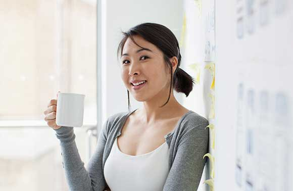 A woman smiling and holding a cup of coffee