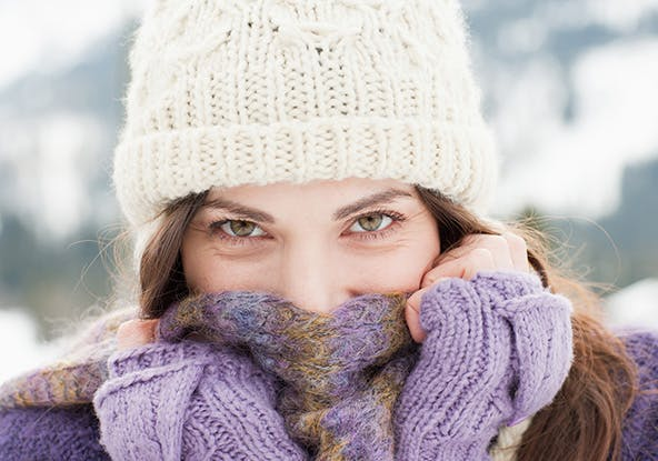 Woman wearing a white winter hat and covering her face with a purple scarf