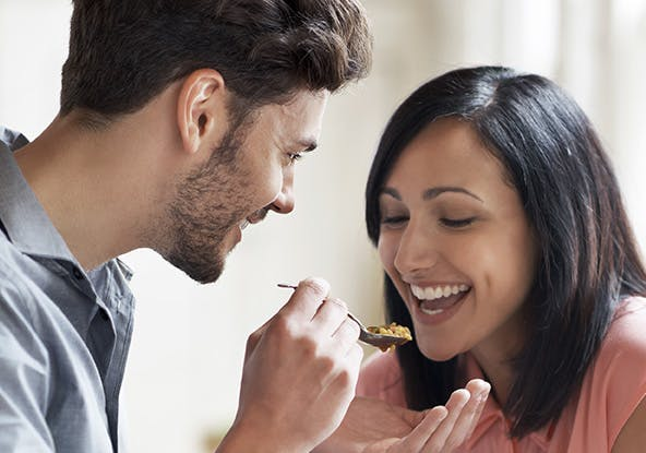 Man sharing his food with a woman from a spoon