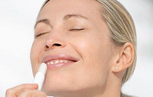 Young woman applying lip balm