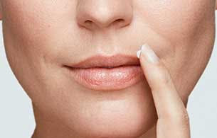Gros plan d'une femme désignant un feu sauvage sur ses lèvres.