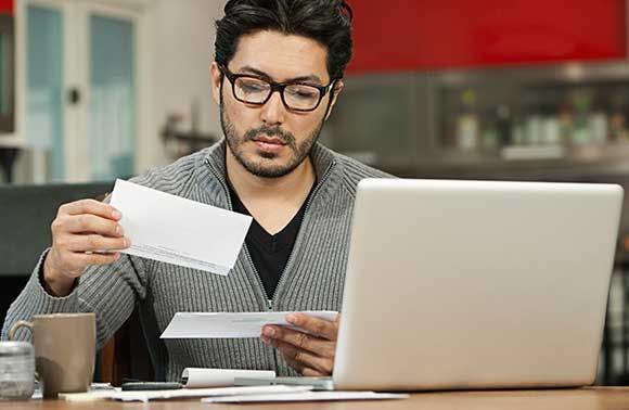Un homme assis à son bureau parcourant le courrier