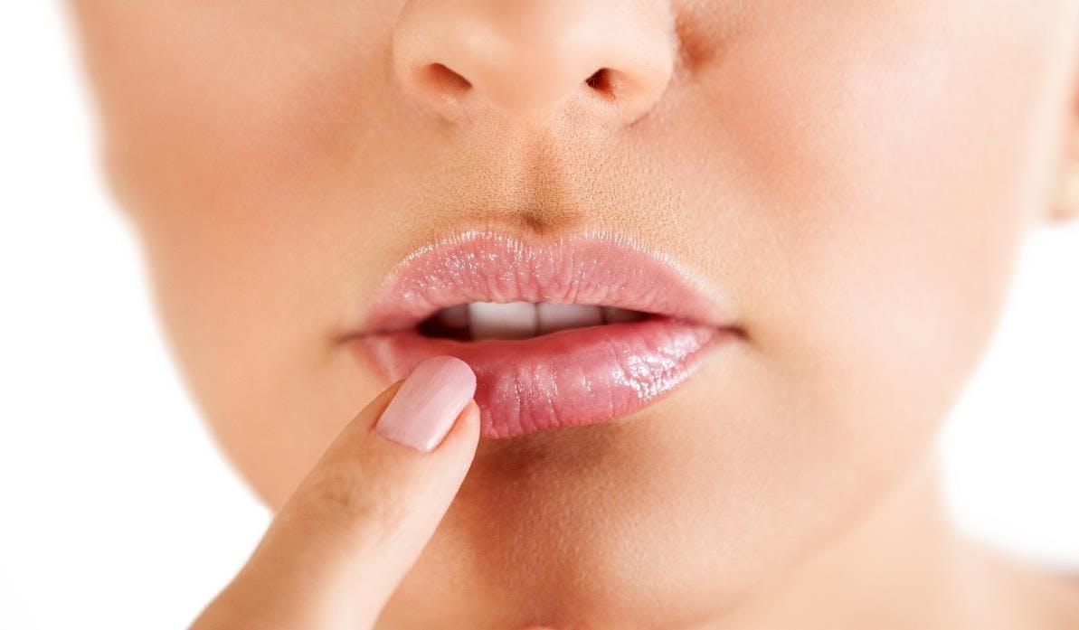 Women touching her lower lip
