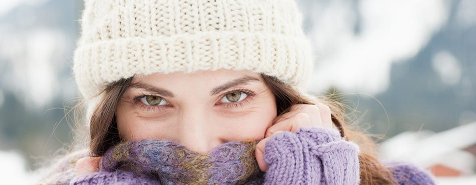 Woman outdoors in a knitted hat holding her scarf over her face