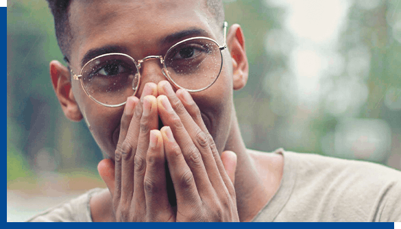 Man in glasses covering his mouth with hands to hide cold sores